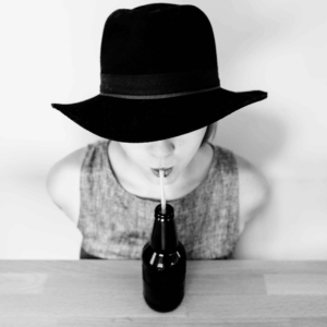 Black and white photo of a woman in a hat drinking with a straw from a bottle